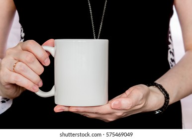 Girl in black dress is holding white cup, mug in hands. Mockup for designs.