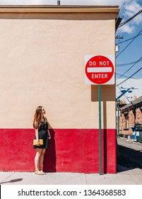 Girl in black dress holding a yellow clutch in front of a red and yellow wall outside on the street downtown looking at a Do Not Enter sign.