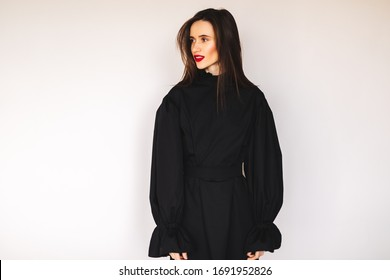 Girl in the black dress laughing. Women health, sexuality. Portrait of a beautiful young woman in black dress with belt and puff sleeves. Sexy brunette woman look happy and smiling. Girl looking away.