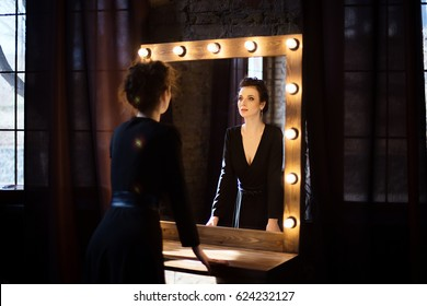 Girl in a black dress looking in the mirror