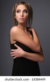 Girl in black dress posing on grey background