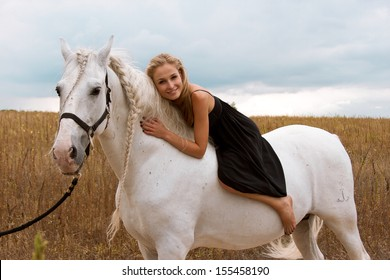 girl in the black dress is riding on a white horse