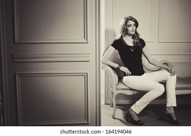 Girl in black dress sitting in old chair studio shoot-black and white