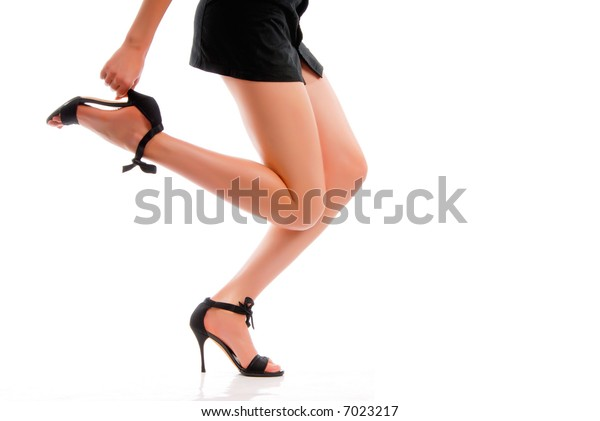 Girl in black dress. We can see only her legs in black shoes on the white background