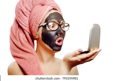 girl with black face mask on the white background, close-up portrait, isolated, pink towel, business woman wearing glasses, girl looks with surprise at herself in a small mirror emotional gender role