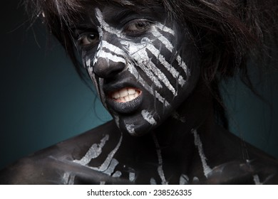 Girl with black face-art. White paint flow on face. Portrait of pretty woman on grey background. Face art and body-art.
