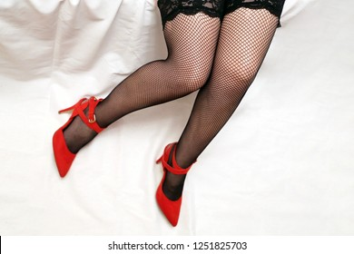 Girl in black fishnet stockings, sexy female legs on white background. Woman in red velvet shoes on high heels, concept of romantic date, Christmas celebration, woman fashion