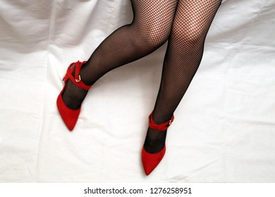 Girl in black fishnet stockings, sexy female legs on white background. Woman in red velvet shoes on high heels, female fashion