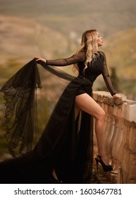 girl in a black flying dress on a background of mountains