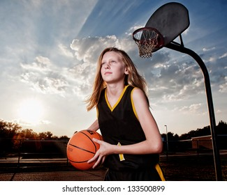 Girl in black and gold basketball uniform with ball, playground hoop and dramatic sky