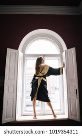 a girl in a black and gold kimono stands on a vintage window with open shutters posing