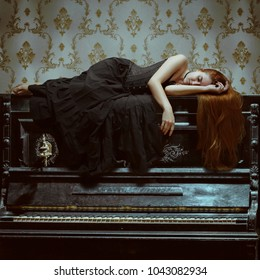 Girl in black gothic dress sleeping on the piano. Sad melody concept