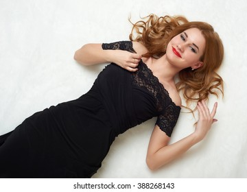 Girl in black gown lying on fur.