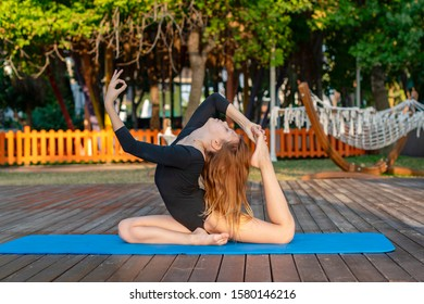 girl in black gymnastic leotard practicing on the street, the concept of yoga and a healthy lifestyle