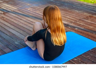 girl in black gymnastic leotard training outdoor and having rest, the concept of yoga and a healthy lifestyle