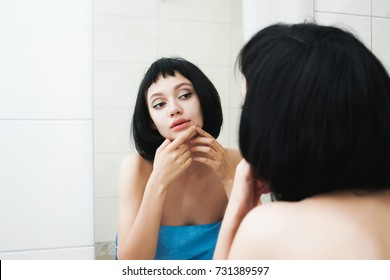 girl with black hair examines her face in the mirror