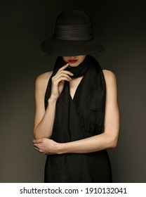 The girl in a black hat holds her fingers on her lips
