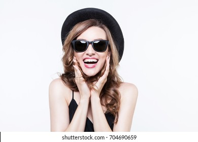 Girl in a black hat and sunglasses. Cheerful girl in cap making faces on camera on white. Indoor portrait of a young beautiful fashionable woman. Female fashion, beauty and advertisement concept.
