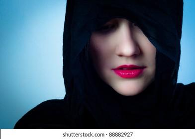 Girl in black hood against blue background