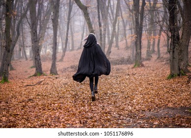 Girl in black hood running away from danger deep in dark forest. Thick fog all around. Scary autumn scene