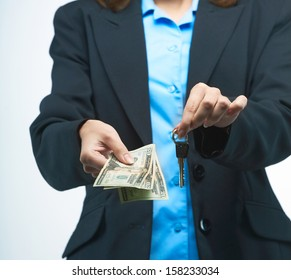 Girl in a black jacket. Holds the money and keys. On a gray background