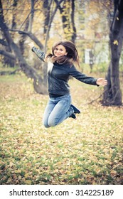 girl in the black jacket jumps in the park in autumn