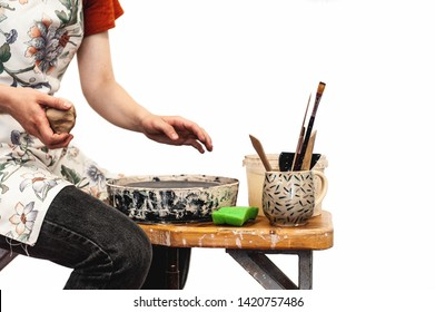 A girl in black jeans, red shirt and white pinafore seating on the wooden bench and holding clay ball in her hand, going to start  doing pottery, tools are located nearby, white isolated
