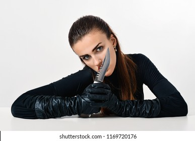 Girl in black with knife. Woman killer. Hitman