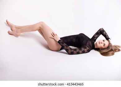 Girl in black lace bodysuit. It lies on a white background. Curly hair