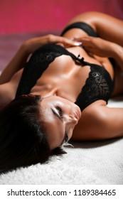 Girl in black lace underwear lying on a white blanket.
