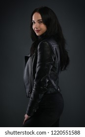 Girl in black leather jacket on dark gray background