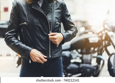 Girl in black leather jacket on background motorcycle in sun flare atmospheric city, hipster biker female hands, motorbike street lifestyle, traveler planing bike route in summer holiday concept