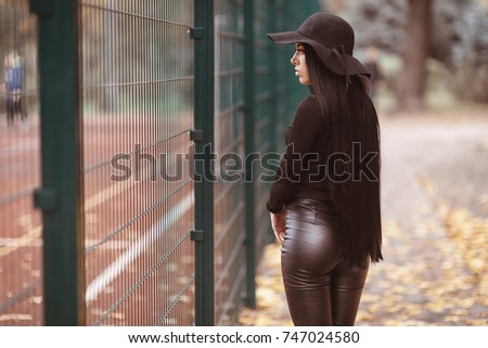 Girl in black leather pants and hat near the fence . Female fashion. City  lifestyle 13e3ebc2c42f
