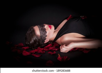 Girl in a black mask with rose petals