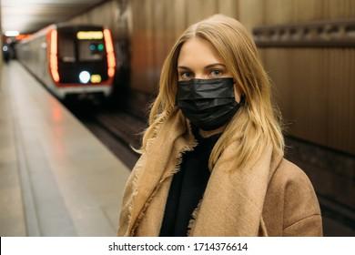 Mädchen in schwarzer medizinischer Maske, die neben dem U-Bahn-Auto stehen. Coronavirus-Epidemie