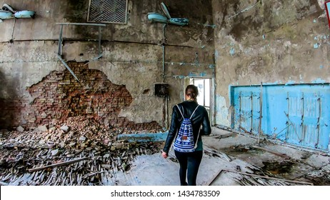 Girl in black outfit walks around the rotten floor in an abandoned sports hall in Pripyat, Ukraine, after the Chernobyl explosion. The floor is completely rotten. Lots of decaying object on the floor