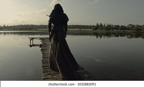 A girl in black rags on an abandoned bridge. Apocalypse. 4k