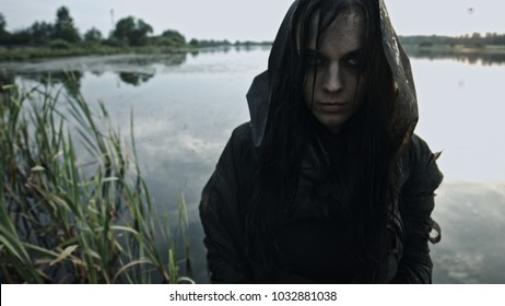 A girl in black rags sits on an abandoned bridge. Apocalypse. 4k
