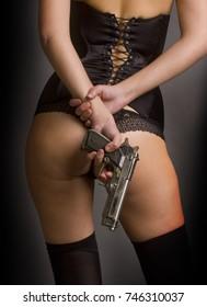 girl in black sexy underwear holds a gun behind her back