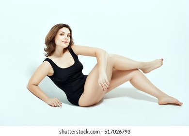 Girl in black swimsuit on a white background. She sits on his side and crossed her legs