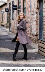 Girl in black tights, beige dress and gray coat, beautiful woman has fun in vintage street, brick wall, funny pretty lady, street photo, flying curly blonde curls, girl spinning in the street