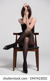 Ein Mädchen in schwarzen Strumpfhosen sitzt auf dem Stuhl. Schöne lange Beine in schwarzen Schuhen.