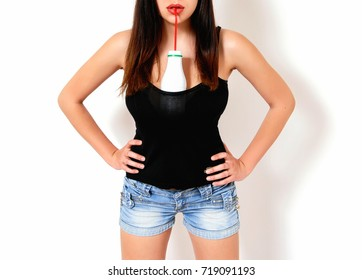 Girl in a black T-shirt and shorts drinks milk from a bottle through a straw.