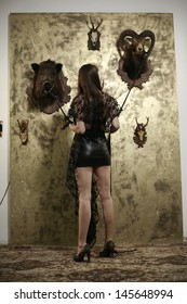 girl in black ,turn in background of a gold wall on which they are hunting trophies