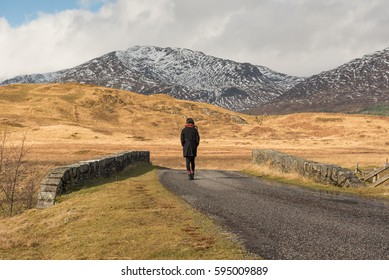 Girl in black wearing a scarf walks away on a road near the Bridge of Orchy, Argyll and Bute, Scotland, UK, where snowy mountains can be seen on a distant valley on the background.