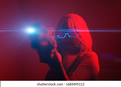 Girl with blaster in the futuristic battle. Concept virtual reality, cyber game and science fiction.