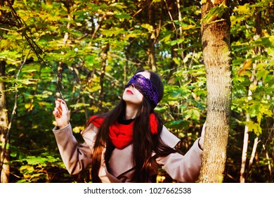A girl with blindfold looks up into the sky in the forest