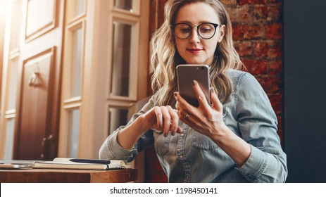 Girl blogger in trendy glasses sits in cafe and uses smartphone,checks e-mail,communicates with followers,reads news, writes message.Freelancer works remotely. Online marketing, education, e-learning.