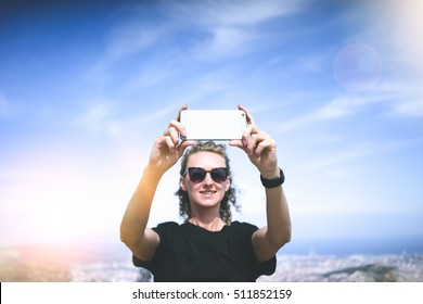 Girl with blond curly hair wearing a black T-shirt and sunglasses, standing on the highest point and take pictures on the smartphone. In background of blue sky and landscape with a bird's eye view.