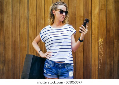 Girl with blond curly hair,dressed in T-shirt and shorts,standing in street and looking at screen of smartphone,is in her hand.In other hand black shopping bag. In background wooden wall. Shopping.